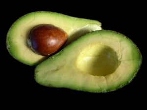 avocado cut in half with brown seed showing green and yellow inside black background Pantothenic Acid Vitamin B5 nutrients from plants