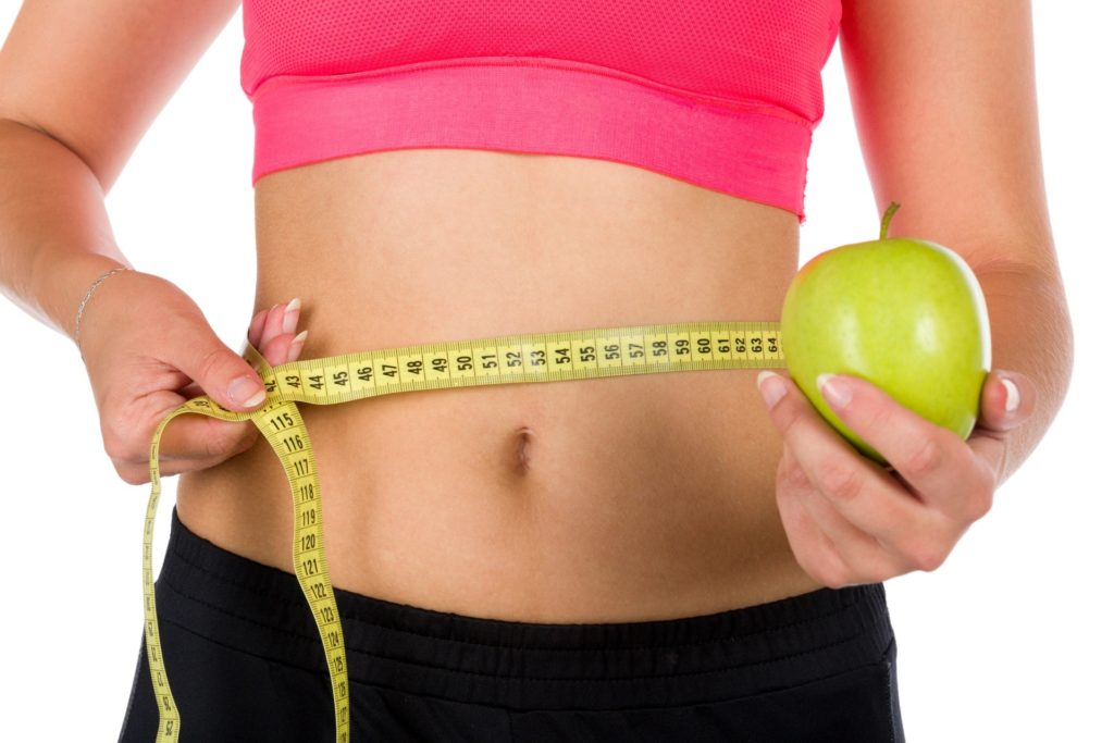 woman holding apple and ribbon tape measure lose weight