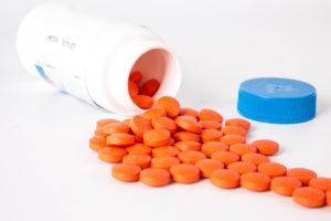 white bottle with red orange circular pills spilling out vitamin B12 B-12 nutrients from plants