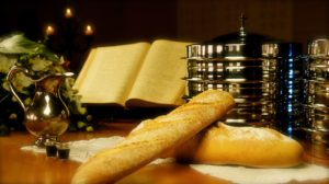 holy supper bread wine on desk with open book