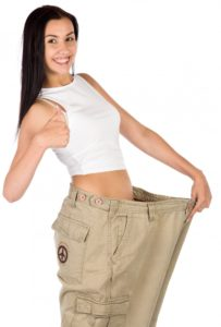 brunette woman in white tank top smiling and giving a thumbs up while holding pants that no longer fit to show weight loss