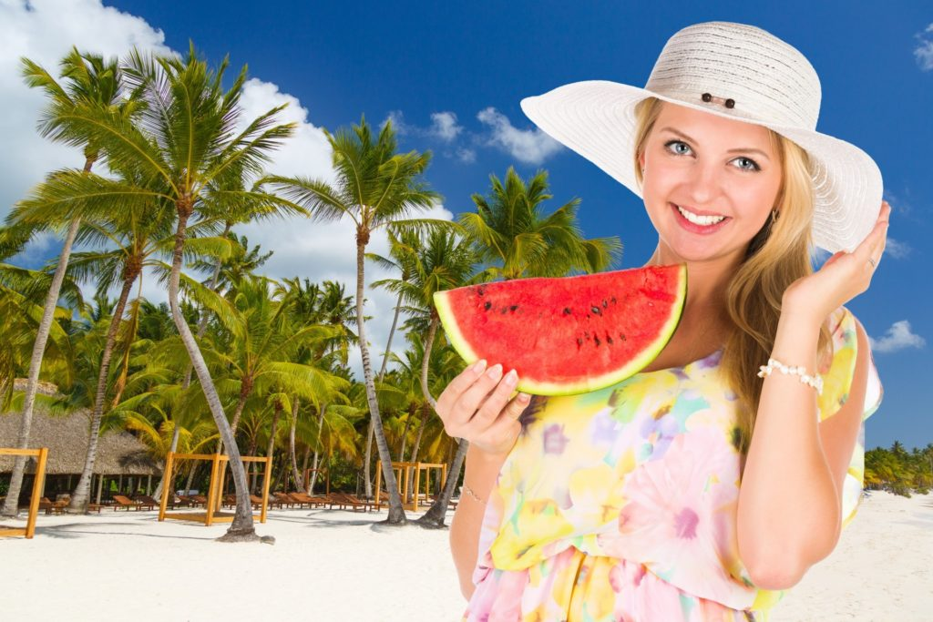 fruits - blonde woman in sun dress and hat on beach holding watermelon