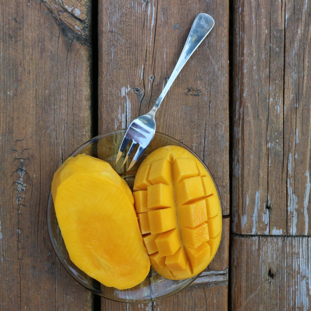 cut mango on a clear plate with a silver fork on top of wood table - foods I avoid