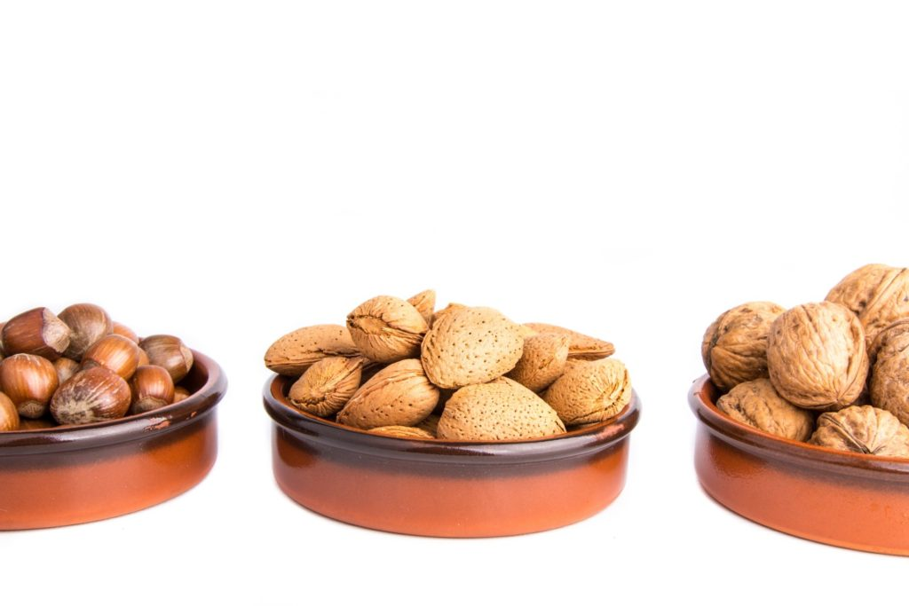 3 types of nuts in separate brown bowls on white background - foods i avoid