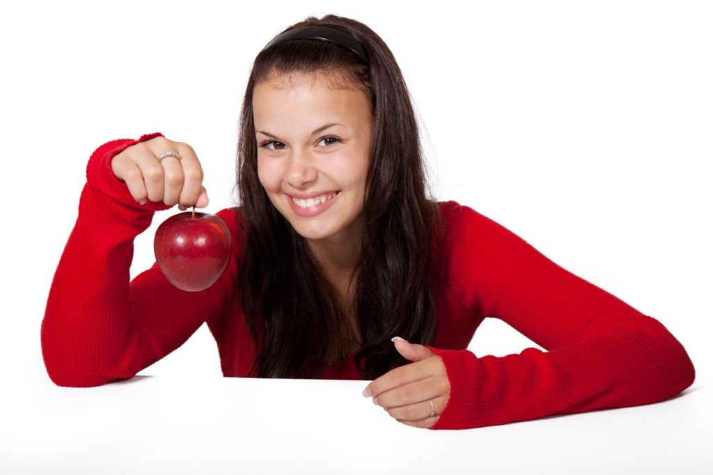 brunette woman in red long sleeve shirt smiling and holding a red apple by the stem plant based diets