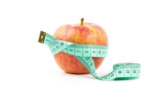 red apple with measuring tape around it