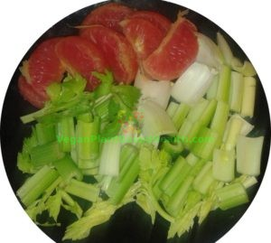 separated grapefruit with cut celery on black plate what i eat in a day