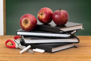 back to school three apples on top of books chalk scissors desk black board chalk board nutrition information health class