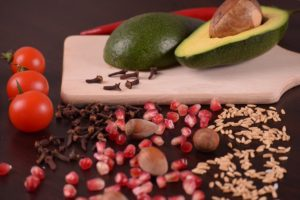 avocado sliced in half on wooden cutting board with nuts and vegetables dietary myths