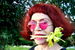hipster woman eating celery red hair pink glasses