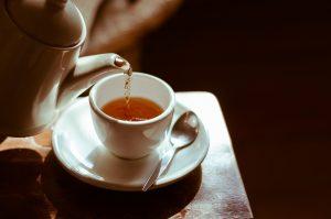 tea kettle pouring green tea into a white tea cup